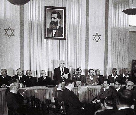 David Ben Gourion proclame la création de l'Etat d'Israël sous le portrait de Theodor Herzl, le 14 mai 1948. Photo Rudi Weissenstein, archives du ministère israélien des affaires étrangères.