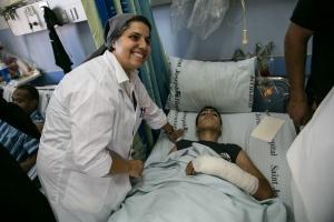 Sr Muna Totah, soeur de St Joseph de l'Apparition, auprès d'un blessé de Gaza accueilli à l'hopital français de Jérusalem