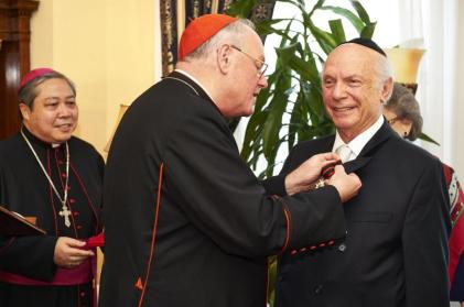 JAMES KEIVOM/NEW YORK DAILY NEWS Timothy Cardinal Dolan pins the Knight of St. Sylvester decoration on Rabbi Arthur Schneier on Monday.